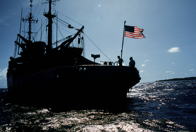 A port quarter view of the salvage ship USS BOLSTER (ARS 38), silhouetted against the sun while underway