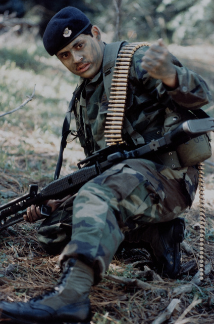 An AIRMAN carrying an M-60 machine gun uses hand signals to communicate during air base ground defense (ABGD) training