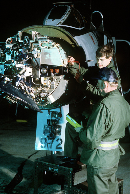 MSGT Bernard Ackerman and SSGT Bruce Adam, 119th Camron (Avionics) section, repair the radar dome on an F-4E Phantom II aircraft during exercise Copper Flag