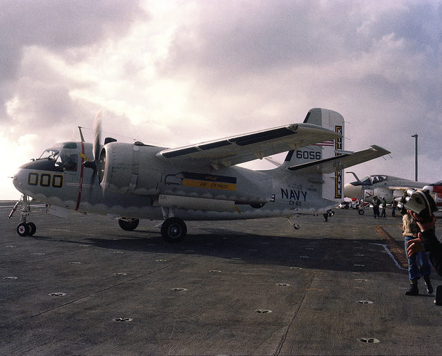 A left side view of a C-1A Trader aircraft on the flight deck of the aircraft carrier USS KITTY HAWK (CV 63). An A-6E Intruder aircraft is visible in the background