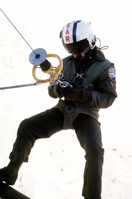 A view of a search and rescue team member as he prepares to rappel from a UH-1N Iroquois helicopter during exercises near Naval Air Station Fallon, Nevada