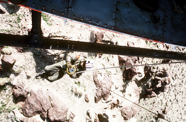 A view of a search and rescue team member as he rappels from a UH-1N Iroquois helicopter during training exercises near Naval Air Station Fallon, Nevada