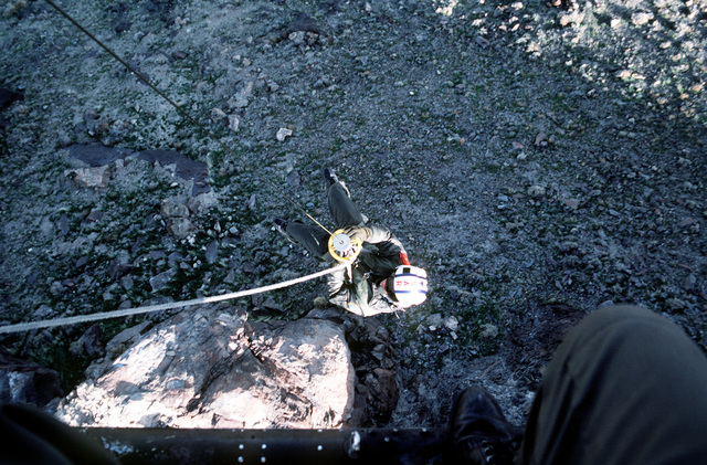 A view of a search and rescue team member as he rappels from a UH-1N Iroquois helicopter during exercises near Naval Air Station Fallon, Nevada