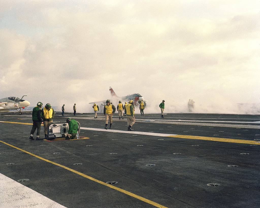 An A-7E Corsair II aircraft moves into position for take-off from the flight deck of the aircraft carrier USS KITTY HAWK (CV 63). An A-6E Intruder aircraft is visible on the left