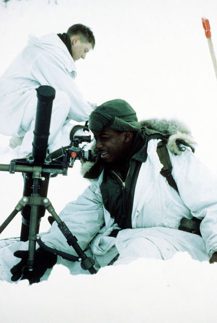 A member of Co. A, 1ST Bn., 2nd Marine Div., sights in a 60mm mortar during Exercise Cold Winter '83