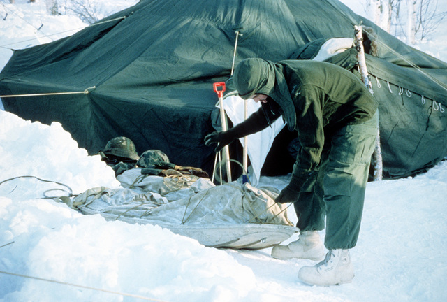 A member of Co. B, 1ST Bn., 2nd Marine Div., unpacks a sled of supplies while setting up a bivouac during Exercise Cold Winter '83