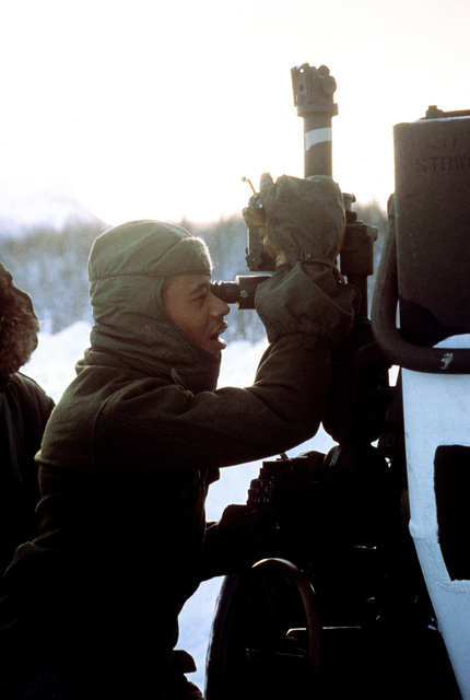 A member of Company B, 10th Marine Regiment, adjusts the elevation of an M-198 155mm medium towed howitzer during Exercise Cold Winter '83