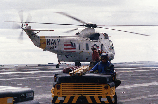 A right side view of an SH-3A Sea King helicopter from Helicopter Anti-submarine Squadron 2 (HS-2) on the flight deck of the aircraft carrier USS KITTY HAWK (CV 63). An MD-3 tow tractor is in the foreground