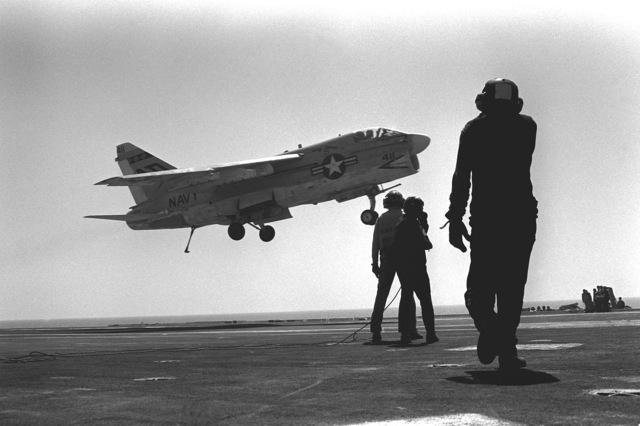 An A-7 Corsair II aircraft prepares to land aboard the aircraft carrier USS KITTY HAWK (CV-63). A catapult officer and two crewmen are seen in the foregorund