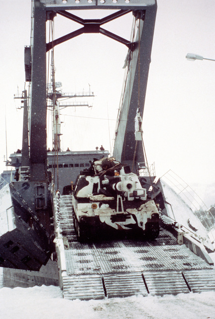 An M-109 self-propelled howitzer is off-loaded from the tank landing ship USS NEWPORT (LST-1179) during Exercise Cold Winter '83
