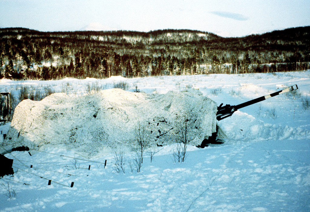 An M-198 155mm medium towed howitzer of the 3rd Battalion, 10th Marine Regiment, is concealed with arctic camouflage during Exercise Cold Winter '83
