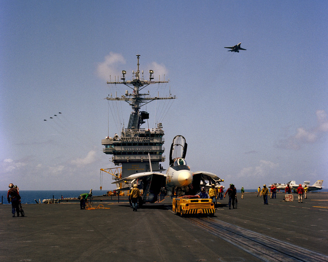 An MD-3A tow tractor is used to tow an F-14A Tomcat aircraft to the catapult track on the flight deck of the nuclear-powered aircraft carrier USS DWIGHT D. EISENHOWER (CVN 69)