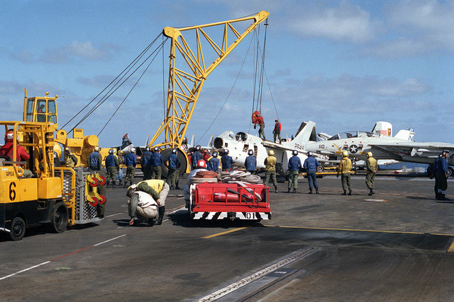 Crewmembers of the aircraft carrier USS KITTY HAWK (CV 63) attach cables from an NS-50 mobile crane to the body of an A-7E Corsair II aircraft during firefighting practice. An MD-3 tow tractor is visible in front of the aircraft