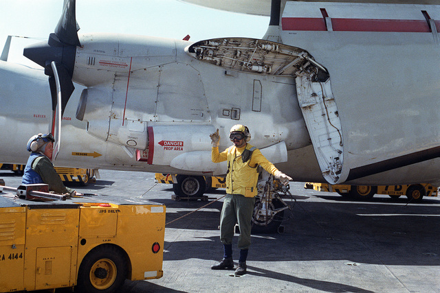 Crewmembers use an MD-3 tow tractor to move aircraft on the flight deck of the aircraft carrier USS KITTY HAWK (CV 63). In the background is an E-3 Hawkeye Airborne Early Warning (AEW) aircraft