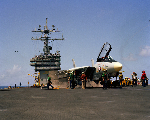 Flight deck crewmen ready an F-14A Tomcat aircraft for launching aboard the nuclear-powered aircraft carrier USS DWIGHT D. EISENHOWER (CVN 69)
