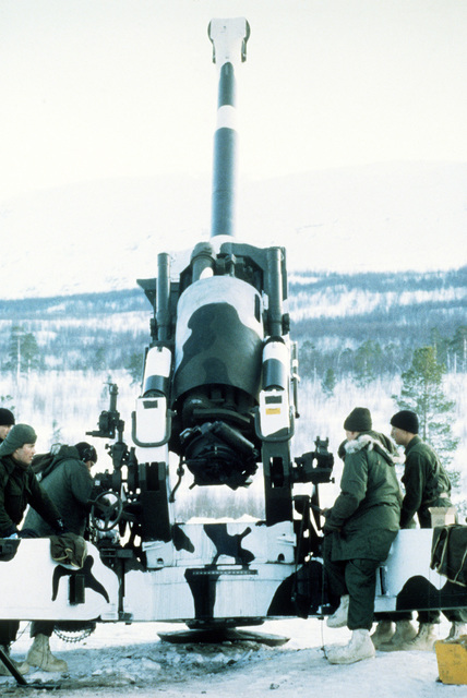 Marines of the 3rd Bn., 10th Marines, 2nd Marine Div., elevate the barrel of an M-198 155mm medium towed howitzer during Exercise Cold Winter '83