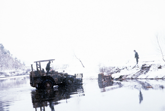 Members of the 25th Infantry Division use a forklift to recover rations from a river during a spring snowstorm. The rations were air dropped by U.S. Air Force C-130 Hercules aircraft during training exercise Team Spirit '83