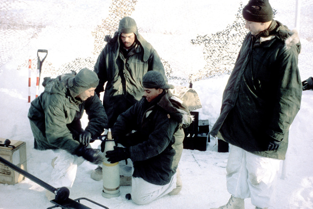 Members of the 3rd Battalion, 10th Marine Regiment, set the detonator fuse on a 155mm projectile for an M-198 medium towed howitzer during Exercise Cold Winter '83