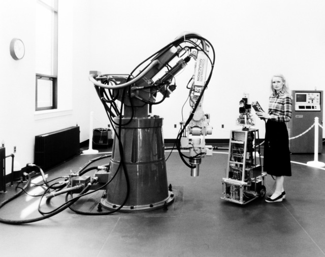 Sharon Hogge, an electronics engineer, poses with autonomous sentry robot ROBART I and the HT3 Industrial Robot (on the left) at the Naval Surface Weapons Center
