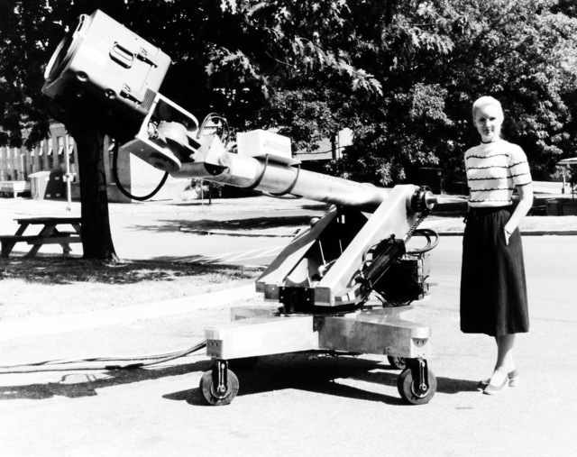 Sharon Hogge, an electronics engineer, poses with heavy-lift hydraulic mobile robot being investigated at the Naval Surface Weapons Center Research and Development Laboratory