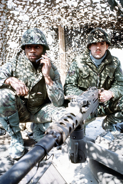 SSGT Ed Garich, left, and SGT Grissam, both of the 51st Security Police Squadron, man a camouflaged .50-caliber machine gun during training exercise Team Spirit '83