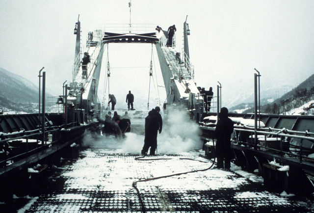 The landing deck of the tank landing ship USS NEWPORT (LST-1179) is steamed free of ice prior to off-loading equipment during Exercise Cold Winter '83