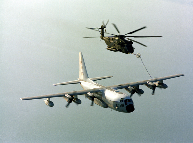 A left front view of a Marine Corps CH-53E Super Stallion helicopter taking on fuel from a Marine Refueler-Transport Squadron 252 (VMGR-252) KC-130R Hercules aircraft during a flight out of Marine Corps Air Station, Cherry Point, North Carolina