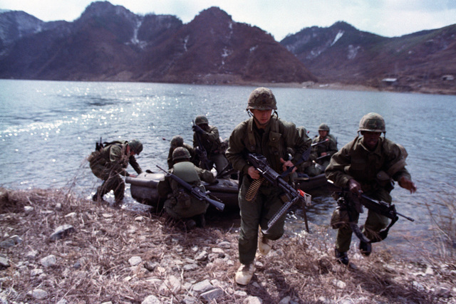 Soldiers of the 1ST Battalion, 27th Infantry, 25th Infantry Division, hit the beach after crossing the Hwachon River in a simulated attack against enemy forces during the joint Korean/United States training exercise TEAM SPIRIT '83