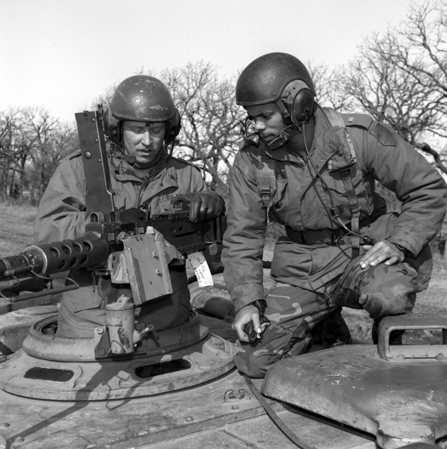 SPECIALIST Fourth Class Richard Pannell (L) instructs Private First Class Robert Roots on how to load and operate the M-2 machine gun mounted on an M-88A1 armored recovery vehicle. Both men are from the 4/37th Armor