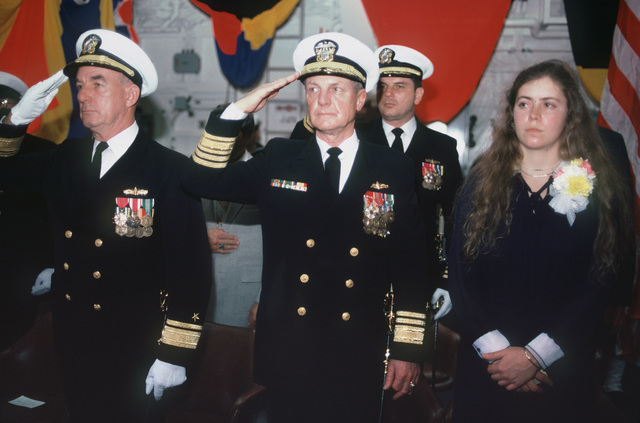 Rear Admiral Richard Berry, commander, Cruiser Destroyer Group Eight, left, and Vice Admiral Edward Briggs, commander, Naval Surface Force, US Atlantic Fleet, salute Distinguished guests salute during the commissioning of the Spruance class destroyer USS HAYLER (DD 997). Standing on the right is Nicole Hayler, sponsor and granddaughter of Admiral Robert Hayler, namesake of the ship