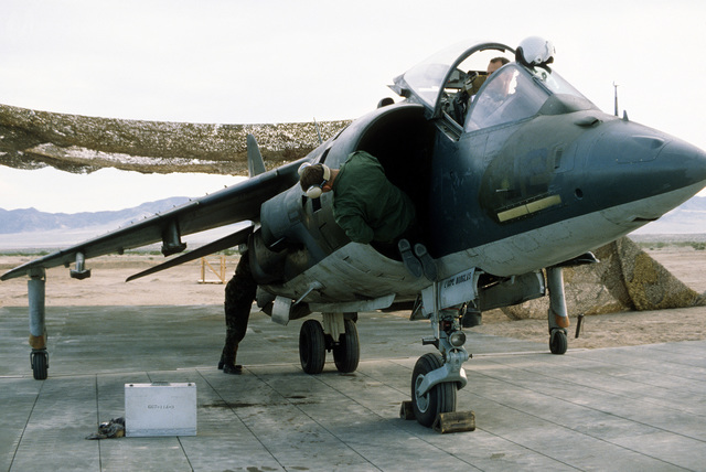 A right front view of an AV-8B Harrier aircraft from Marine Light Attack Squadron 513 (VMA-513). Flight service personnel perform maintenance on the Harrier during Operation Comfort