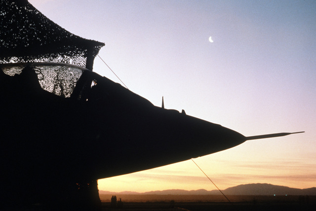 The sun sets on an AV-8B Harrier aircraft from Marine Light Attack Squadron 513 (VMA-513) parked under a net on a portable runway during Operation Comfort