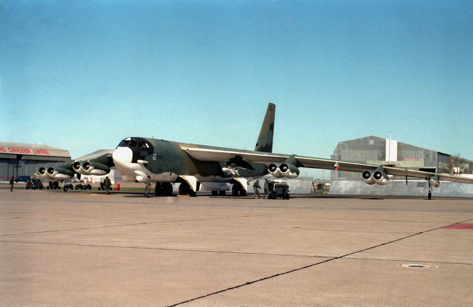 A right front view of a B-52 Stratofortress aircraft with a Harpoon (AGM-84A) missile on its wing, as it is prepared for takeoff. This is the first launch of a Harpoon from a B-52