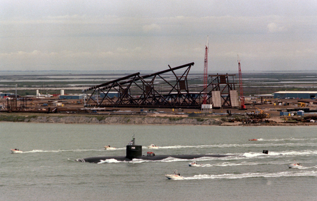 A port view of the nuclear-powered attack submarine USS CITY OF CORPUS CHRISTI (SSN 705) being escorted by small boats as it sails through Corpus Christi Bay during its first visit to its namesake city