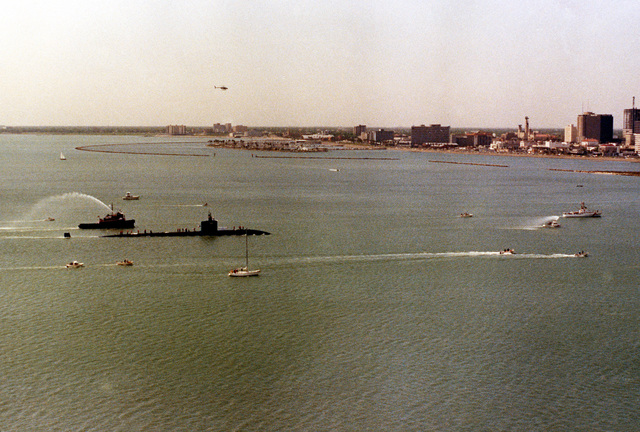 A starboard beam view of the nuclear-powered attack submarine USS CITY OF CORPUS CHRISTI (SSN-705) being escorted by small boats and harbor tugboats as it sails through Corpus Christi Bay during its first visit to its namesake city