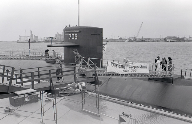 Visitors cross the brow of the nuclear-powered attack submarine USS CITY OF CORPUS CHRISTI (SSN 705) while the vessel is tied up at a pier.  This is the ship's first visit to its namesake city