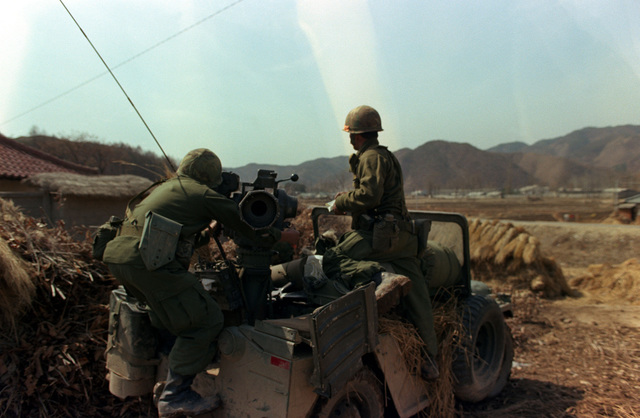 Private First Class Clifton Burden and Sergeant Anthony Atuigue of the Combat Support Company, 1ST Battalion, 5th Infantry Division, position a TOW missile system in Yang Deog Village against attacking Blue Forces, during the joint South Korean/US training Exercise TEAM SPIRIT `83