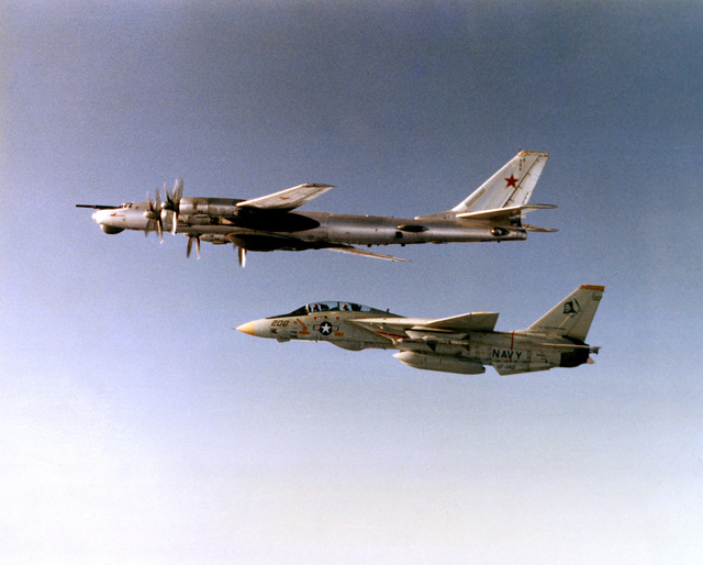 A left side air-to-air view of a Soviet Tu-95 Bear maritime reconnaissance aircraft, top, being escorted by a U.S. Navy F-14 Tomcat aircraft as the Soviet aircraft approaches the Readex 1-83 battle group. LCDR Greg Quist pilots the Fighter Squadron 142 (VF-142) Tomcat, assigned to the nuclear-powered aircraft USS DWIGHT D. EISENHOWER (CVN-69). LT J.G. Randy Dewar is the radar intercept officer