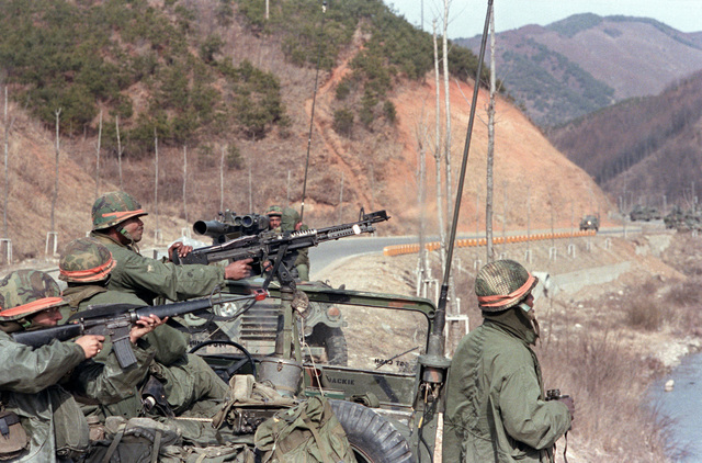 Members of Company B, 1ST Battalion, 5th Infantry Division (Orange Forces), defend their position on a roadside against advancing Blue Forces during the joint Korean/United States training exercise TEAM SPIRIT '83