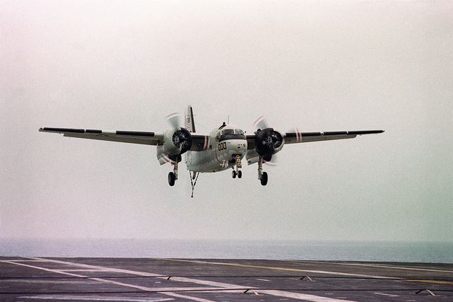 A C-1A Trader cargo/transport aircraft approaches for landing aboard the aircraft carrier USS KITTY HAWK (CV 63). The tailhook on the aircraft is down to catch the arresting gear on the flight deck of the carrier