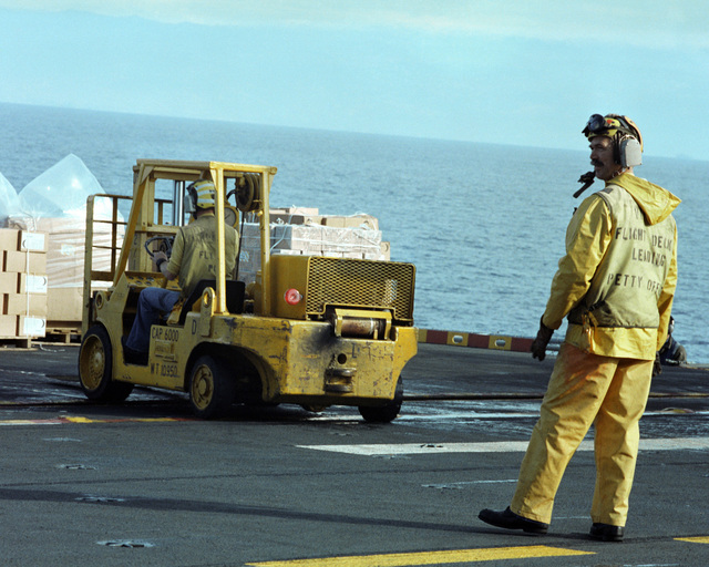 A flight deck crewman supervises a forklift operator aboard the amphibious assault ship USS GUAM (LPH 9), stationed off the coast of Beirut. The ship is providing support to US Marines deployed in Lebanon as part of a multi-national peacekeeping force following confrontation between Israeli forces and the Palestine Liberation Organization