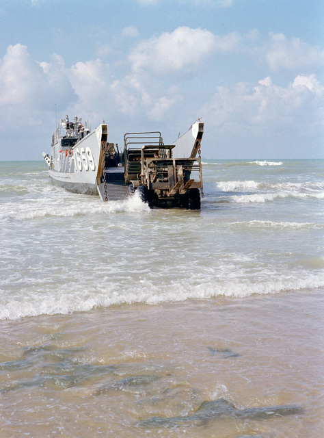 A rough terrain forklift loads materials onto a utility landing craft (LCU 1659). The loading operations are part of the 24th Marine Amphibious Unit's departure from Beirut. The Marines have been deployed in Lebanon as part of a multi-national peacekeeping force following confrontation between Israeli forces and the Palestine Liberation Organization
