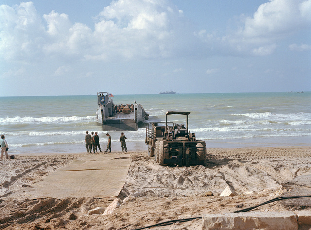 A rough terrain forklift transports material to a waiting utility landing craft. The loading operations are being conducted prior to the 24th Marine Amphibious Unit's departure from Beirut. The Marines have been deployed in Lebanon as part of a multi-national peacekeeping force following confrontation between Israeli forces and the Palestine Liberation Organization