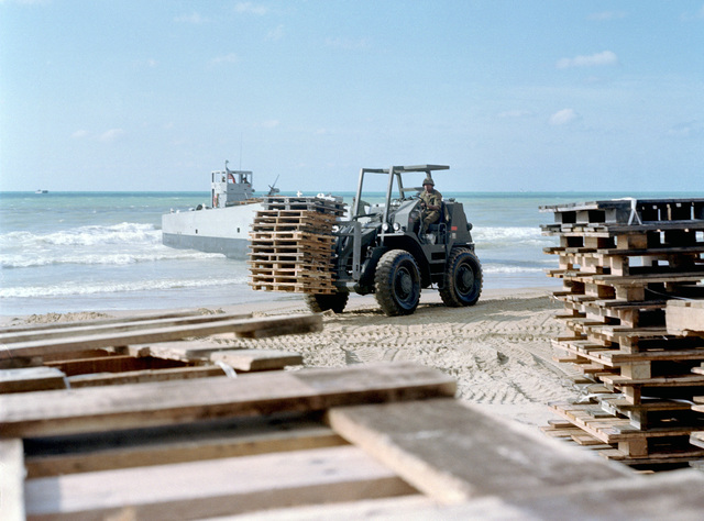A rough terrain forklift transports wooden platforms at the 24th Marine Amphibious Unit's beachfront encampment. A utility landing craft is visible in the background. The Marines have been deployed in Lebanon as part of a multi-national peacekeeping force following confrontation between Israeli forces and the Palestine Liberation Organization