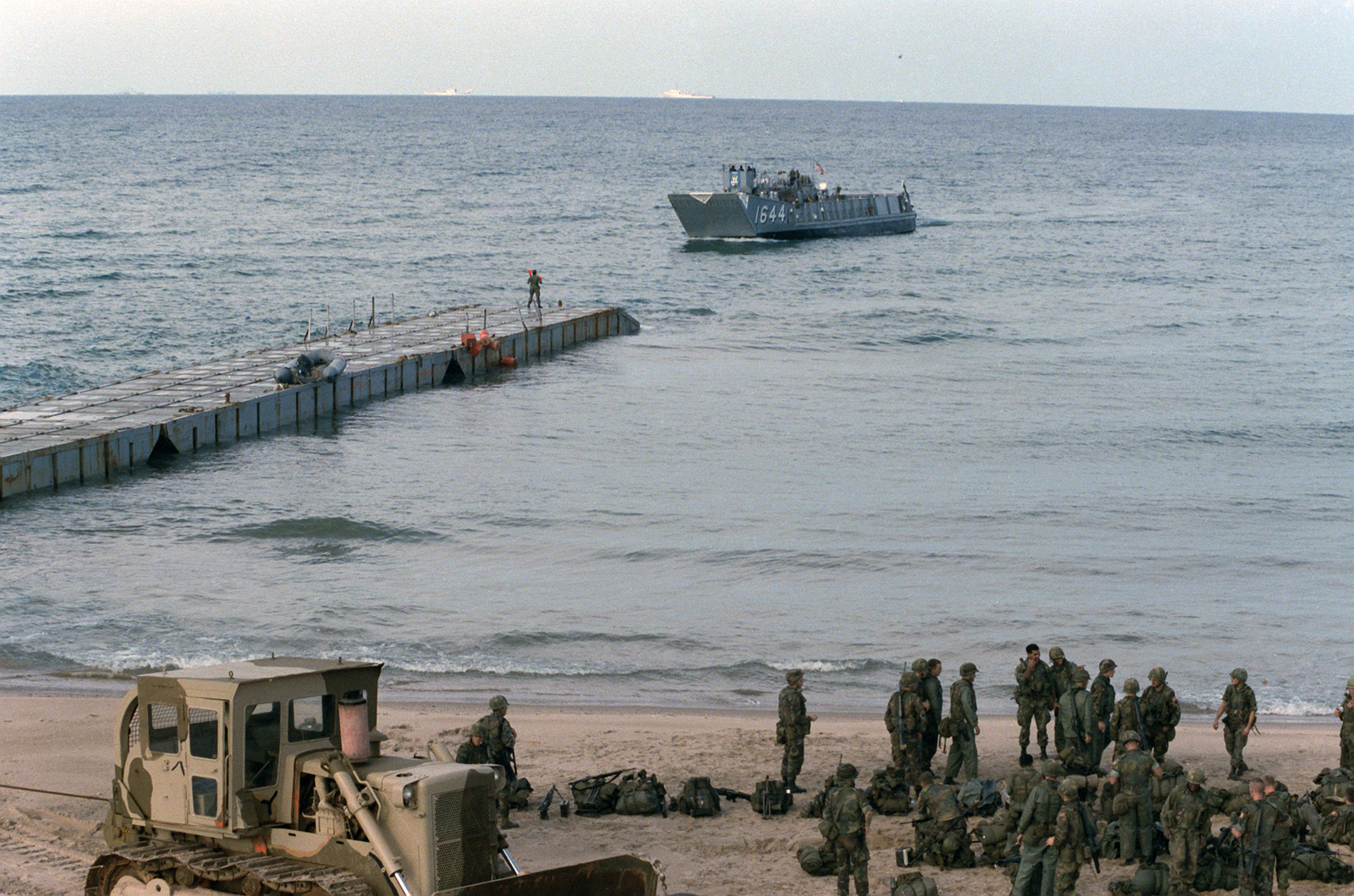 A utility landing craft approaches a causeway as US Marines