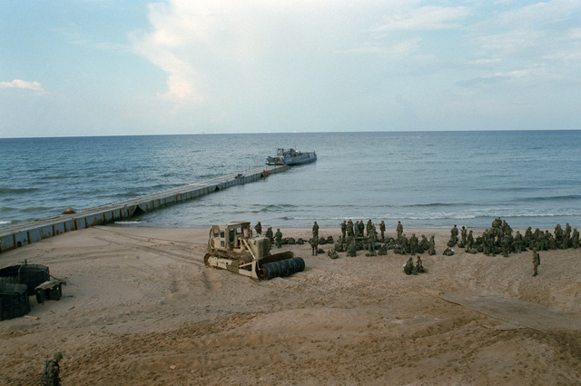 A utility landing craft approaches a causeway as US Marines wait onshore. The Marines have been deployed in Lebanon as part of a multi-national peacekeeping force following confrontation between Israeli forces and the Palestine Liberation Organization