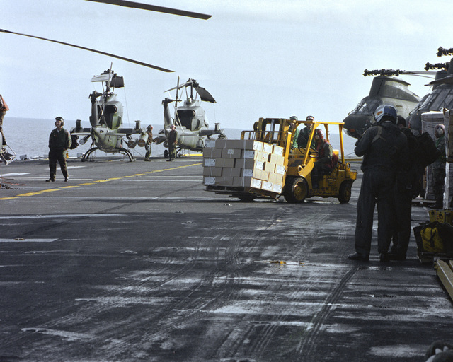 AH-1T Sea Cobra helicopters and CH-46 Sea Knight helicopters line the flight deck as a forklift operator moves cargo aboard the amphibious assault ship USS GUAM (LPH-9), stationed off the coast of Beirut. The ship is providing support to U.S. Marines deployed in Lebanon as part of a multi-national peacekeeping force following confrontation between Israeli forces and the Palestine Liberation Organization