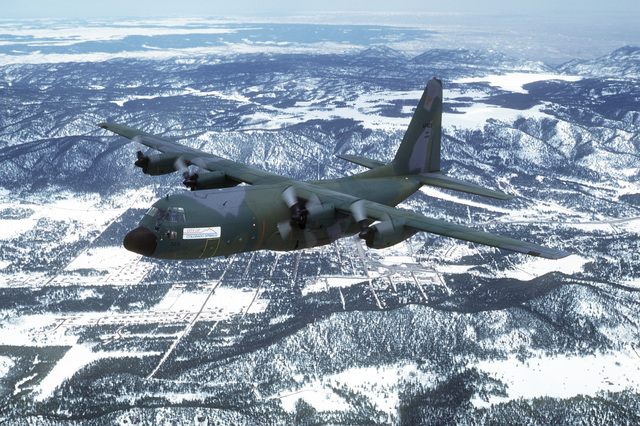 "An air-to-air left side view of a 901st Tactical Airlift Group, Air Force Reserve, C-130 Hercules aircraft with a ""City of Colorado Springs"" sign on the fuselage. Colorado Springs is visible below"