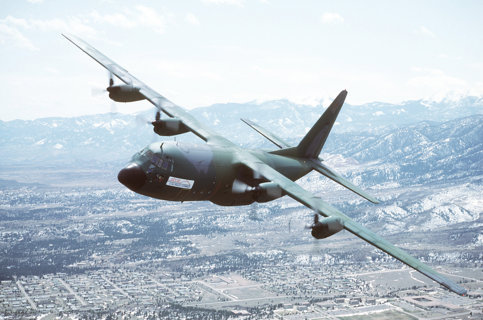 "An air-to-air left side view of a 901st Tactical Airlift Group, Air Force Reserve, C-130 Hercules aircraft with a ""City of Colorado Springs"" sign on the fuselae. The US Air Force Academy is visible below"