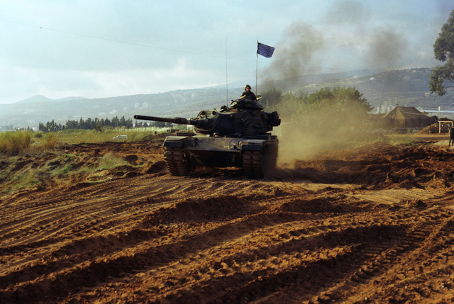 An M60 main battle tank monitors a US Marine Corps encampment on the outskirts of Beirut. The Marines have been deployed in Lebanon as part of a multi-national peacekeeping force following confrontation between Israeli forces and the Palestine Liberation Organization